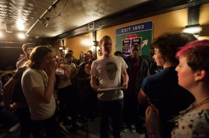 Slam host Sean Patrick Mulroy protects the poets from the piercing stares of the judges. Photo by Marshall Goff.