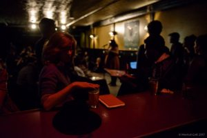 Chloé Cunha listens in from the bar at the Cantab. Photo by Marshall Goff.