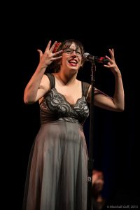 Split This Rock winner Sara Brickman, pictured here showcasing on the National Poetry Slam Finals Stage. Photo by Marshall Goff.