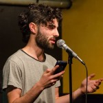 Josh Elbaum takes the stage to sacrifice for the open slam. Photo by Rich Beaubien.