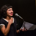 Melissa Lozada-Oliva takes a moment between poems during her feature set. Photo by Rich Beaubien.
